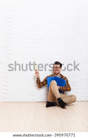 Business Man Sit On Floor Point Pencil To Copy Space Hold Folders Office Over White Brick Wall - stock photo