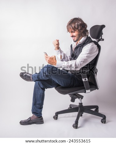 Business man sitting and celebrating succes and good news. - stock photo