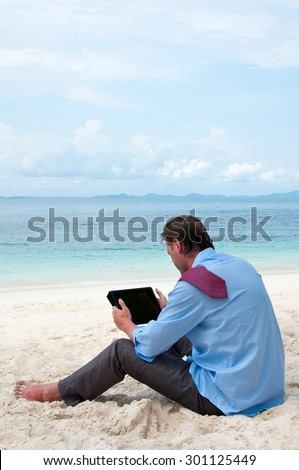 Business man sitting and working on the beach with tablet computer - stock photo