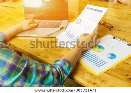 Business man sitting at beautiful wooden desk and using digital computer while typing something on keyboard,freelancer working with laptop in home interior, morning light,selective focus,vintage color - stock photo