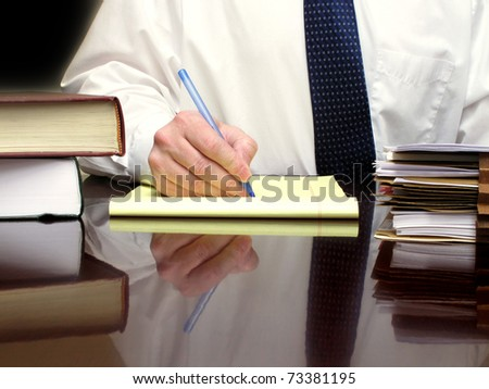 Business Man sitting at desk holding pen with files - stock photo