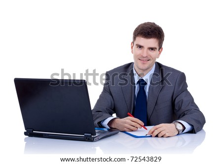Business man sitting at desk, writing notes on paper, smiling. Isolated on white background - stock photo