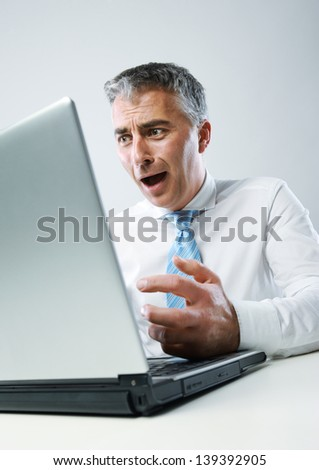 Business man sitting at his desk panics in front of his computer - stock photo