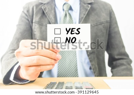 business man sitting at office desk word Yes or No on white card - stock photo