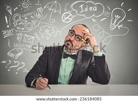 Business man sitting at table has many ideas things to do planning future isolated grey office wall background. Perception of career. Personal life work balance concept. Decision making process - stock photo
