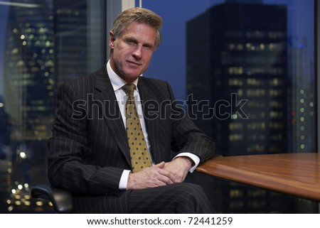 Business man sitting at table in boardroom looking at camera