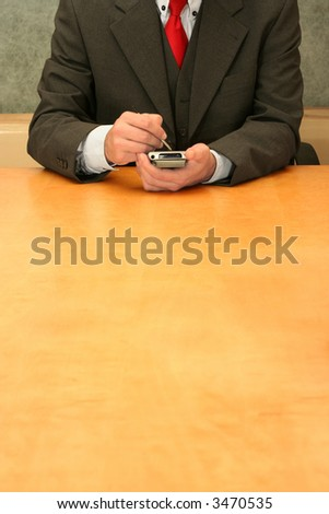 Business-man sitting at the desk, checking his PDA. - stock photo
