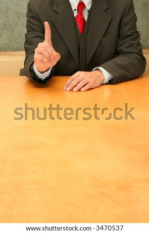 """Business-man sitting at the desk, fingers indicating """"first"""". - stock photo"""