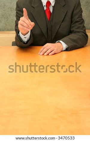 Business-man sitting at the desk, gesturing with his hand. - stock photo