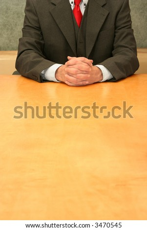 Business-man sitting at the desk, hands crossed.