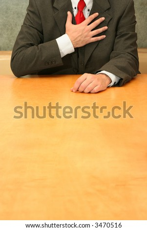 Business-man sitting at the desk, hands to his heart. - stock photo