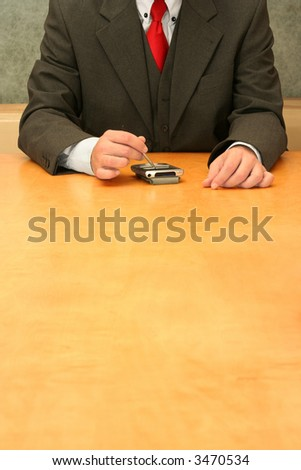 Business-man sitting at the desk, making calculations with his PDA. - stock photo