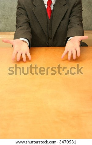 Business-man sitting at the desk, open hands. - stock photo