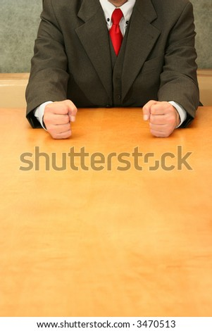 Business-man sitting at the desk, showing both fists. - stock photo