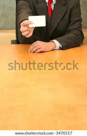 Business-man sitting at the desk showing his business card. - stock photo