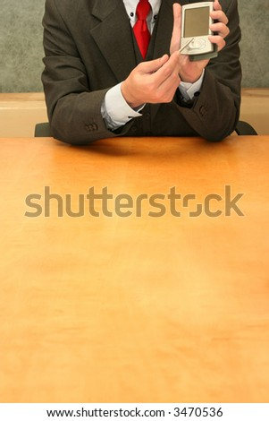 Business-man sitting at the desk showing his PDA. - stock photo
