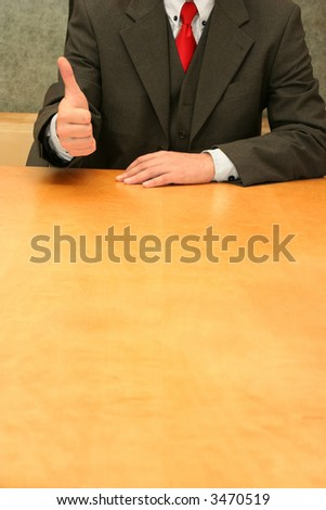 Business-man sitting at the desk, signaling it is OK! - stock photo
