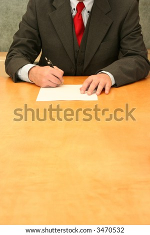 Business-man sitting at the desk, signing document. - stock photo