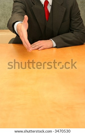 Business-man sitting at the desk wanting to shake your hand. - stock photo