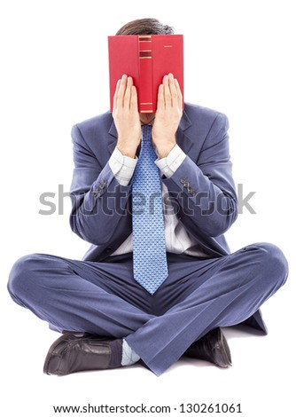 Business man sitting cross legged covering his face with a book on white - stock photo