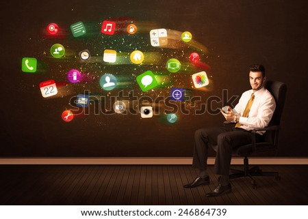 Business man sitting in office chair with tablet and colorful app icons concept on background - stock photo