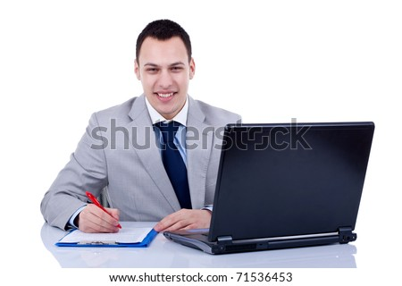 Business man sitting in office with laptop writing note - stock photo