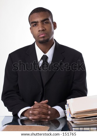 Business man sitting next to a pile of paperwork. - stock photo