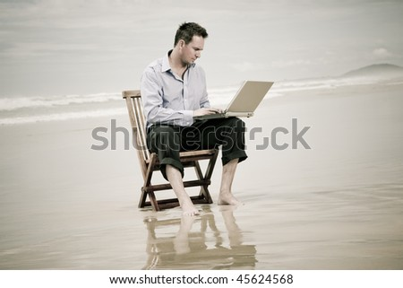 business man sitting on a chair on the beach with laptop - stock photo