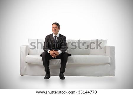 business man sitting on a white modern sofa - stock photo