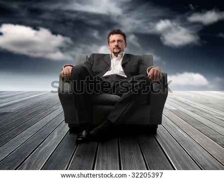 business man sitting on armchair  against a sky - stock photo