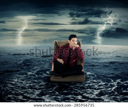Business man sitting on armchair in the ocean water. Danger concept.