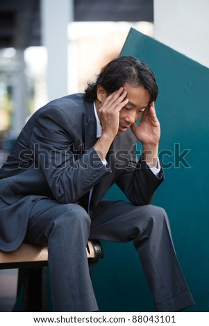 Business man sitting on bench outdoors not feeling well - stock photo