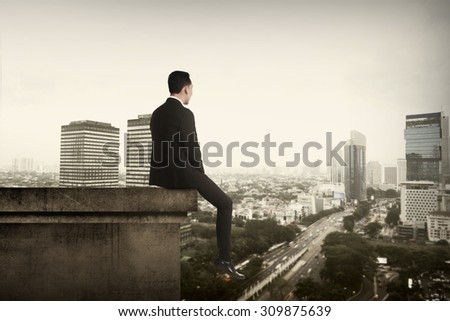Business man sitting on building rooftop. Suicide concept image - stock photo