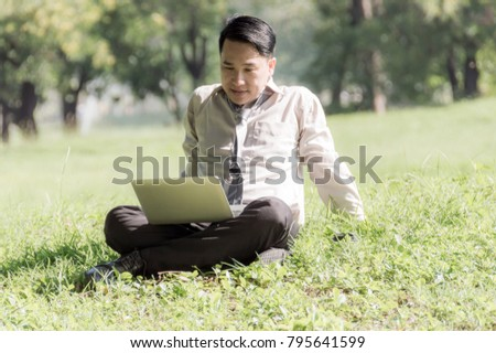 Business man sitting on green grass in the park, Looking information and business profits from notebook.