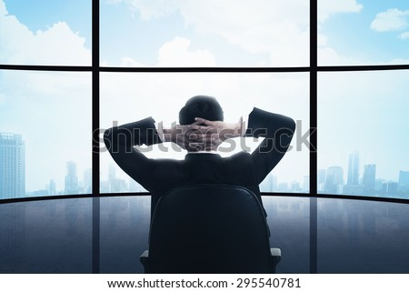 Business man sitting on the chair looking the window. Business success conceptual