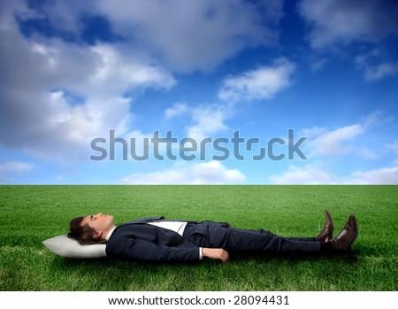 Business man sleeping on a grass field - stock photo