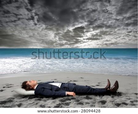 Business man sleeping on the beach - stock photo