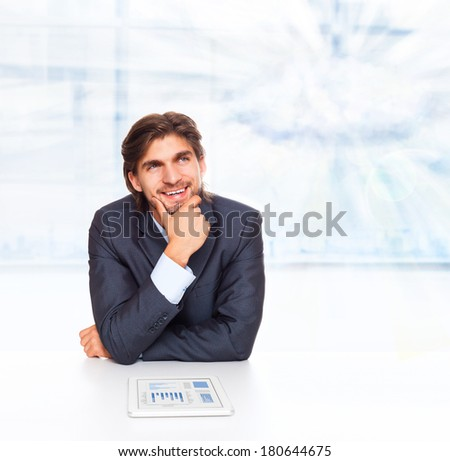 business man smile think look up white cloud with copy space sitting at desk with tablet computer, handsome young businessman ponder, concept of idea, hold hand finger on chin - stock photo