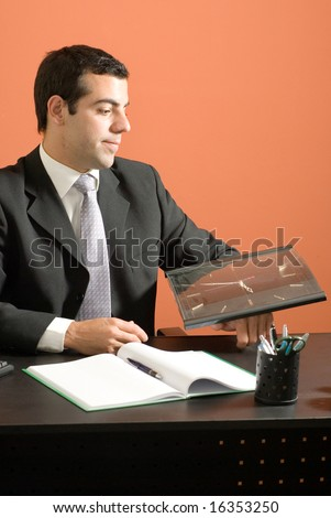 Business man smiles as he sits at his desk looking at his clock. Vertically framed photo. - stock photo