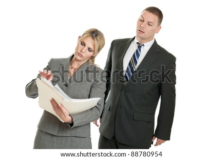 Business man sneaking a look at a business woman's papers isolated on a white background - stock photo