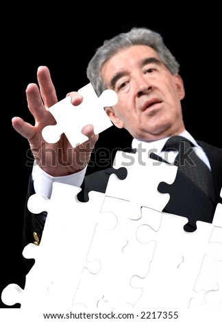 business man solving a puzzle over a black background - stock photo