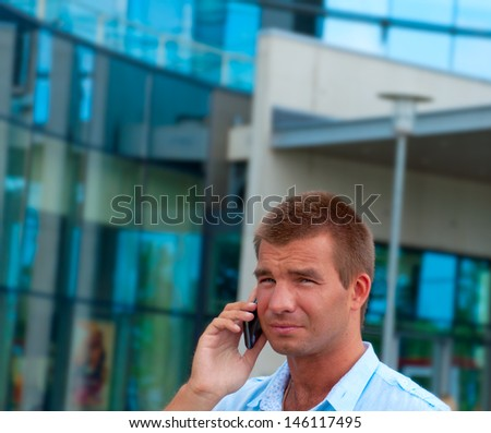 Business man speaking on phone in front of modern business building.