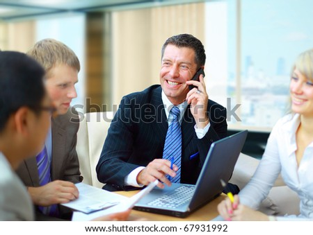 business man speaking on the phone while in a meeting - stock photo