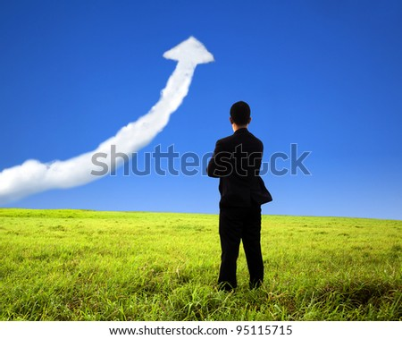 business man stand on the field and watch growth graph cloud - stock photo