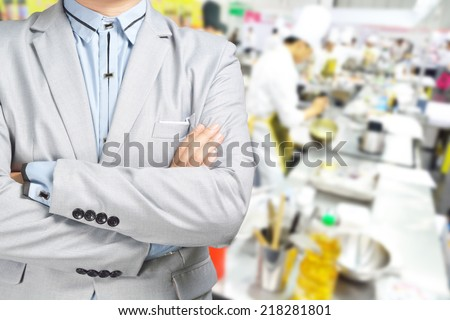 Business Man standing against the Background of Kitchen as Concept of Restaurant , Catering or Food service. - stock photo