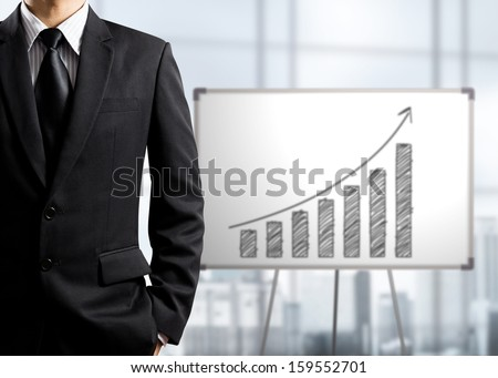 Business man standing and drawing growth chart on white board, success concept - stock photo