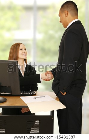 business man standing and shake hand with business woman. concept for office related, business deal, or team work - stock photo