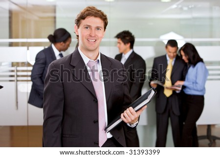 Business man standing at an office holding a portfolio