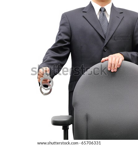 Business man standing behind an office chair holding a pair of handcuffs, isolated on a white background. - stock photo