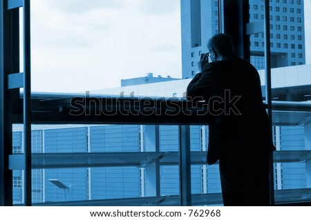 Business man standing by the window - stock photo
